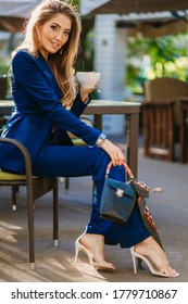 attractive stylish woman dressed in blue elegant suit sitting at table in cafe drinking cup of cappuccino, autumn fashion trend, elegant footwear shoes on heel