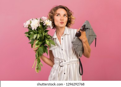 attractive stylish woman in elegant white striped dress on pink studio background with emotional funny face expression holding handbag, sunglasses and flower bouquet, fashion summer trend accessory