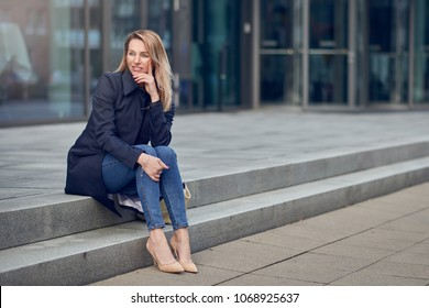 Attractive stylish woman in high heels and an overcoat sitting on urban steps looking thoughtfully to the side with her chin on her hand