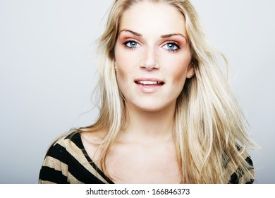 Attractive stylish woman with long blond hair looking directly at the camera with parted lips, head and shoulder portrait on grey