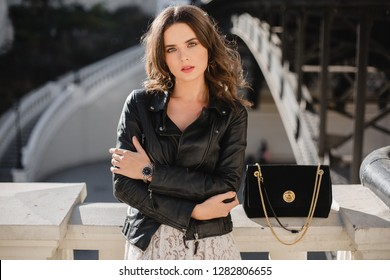 attractive stylish woman posing in street in fashionable outfit with suede handbag wearing black leather jacket, spring autumn style
