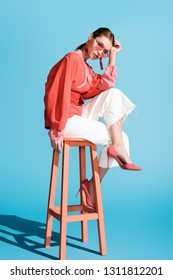 attractive stylish woman in trendy living coral clothing and sunglasses posing on stool on blue