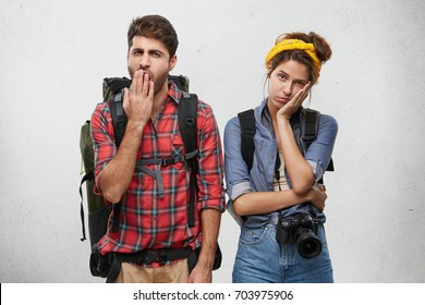 Attractive stylish young couple of European travelers feeling bored or tired: unshaven man covering mouth while yawning, his girlfriend looking at camera with bored disinterested expression