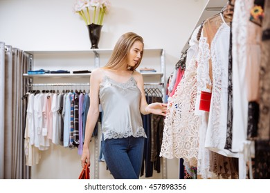 Attractive stylish young woman choosing clothes in shop