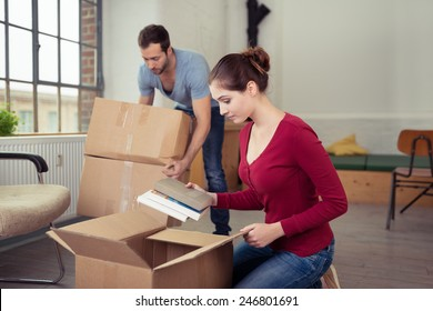 Attractive stylish young woman unpacking a removals carton on the floor of their new home as her husband arrives with two more