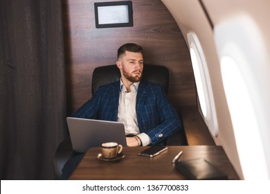 Attractive and successful businessman working on a laptop while sitting in a chair of his private jet.