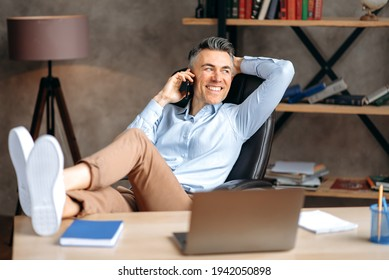 Attractive successful gray-haired businessman, freelancer or manager is talking the phone, calling friends or colleagues, throwing his feet on the table, relaxing office, looks away, smiling happily