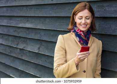 Attractive, successful and happy middle aged woman female using mobile cell phone for texting or social media