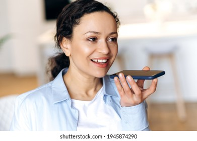 Attractive successful mixed race brunette attractive woman, using smartphone, talking to friends or colleagues on speakerphone or recording audio message, looking away, smiling friendly - Shutterstock ID 1945874290