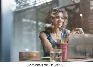 Attractive successful modern young businesswoman smm manager create new online post promote cafe sit window bar drink coffee look pleased laptop screen, working freelance, reading interesting article