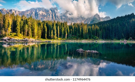 Attractive summer view of Carezza (Karersee) lake. Amazing morning scene of Dolomiti Alps, Province of Bolzano, South Tyrol, Italy, Europe. Beauty of nature concept background.
