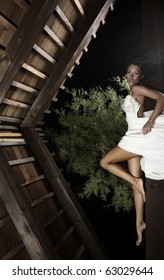 Attractive suntanned girl in white dress poses on a wooden beam.