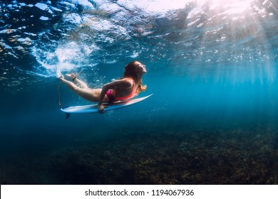 Attractive surfer girl dive underwater with wave.