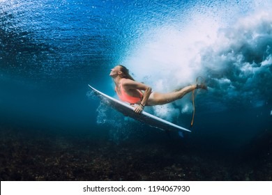 Attractive surfer woman dive underwater with under wave.