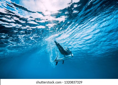 Attractive surfer woman dive underwater with under wave in blue ocean.