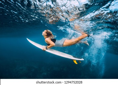 Attractive surfer woman with surfboard dive underwater with under wave.