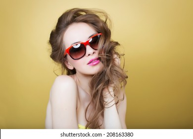 658ca1293426f Attractive surprised young woman wearing sunglasses on gold back