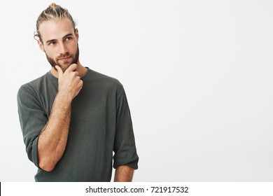 Attractive swedish guy with stylish hair and beard in grey shirt holding his chin and thoughtfully looking aside thinking about his future.
