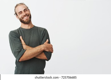 Attractive swedish man with stylish hair and beard laughs at funny story from friend with crossed hands and closed eyes.