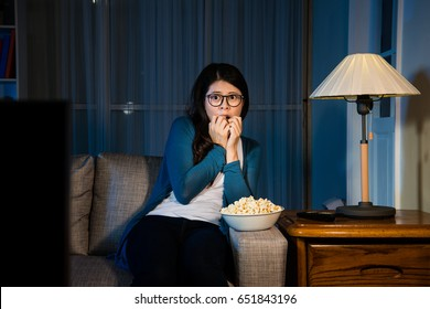 attractive sweet woman sitting on comfortable sofa couch showing afraid emotional with gesture when she watching horror movie at night alone.