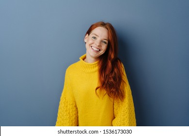 Attractive sweet young woman with a lovely gentle smile tilting her head as she looks at the camera over a blue studio background with copy space
