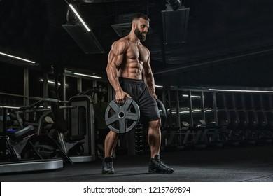 Attractive tall muscular bodybuilder doing heavy deadlifts in moder fitness center.