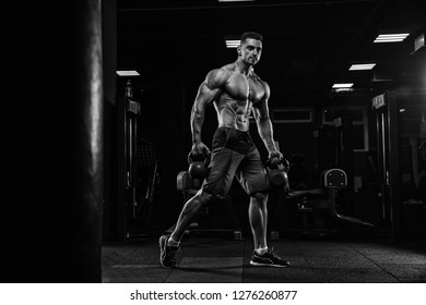 Attractive tall muscular bodybuilder doing heavy deadlifts in moder fitness center