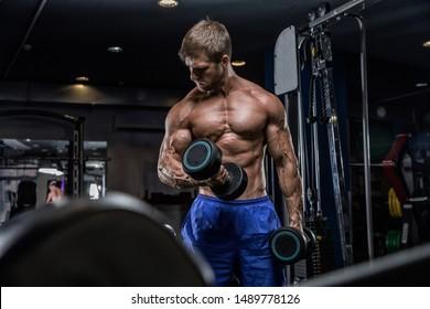 Attractive tall muscular bodybuilder doing heavy deadlifts