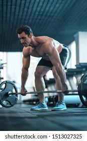 Attractive tall muscular bodybuilder doing heavy deadlifts in moder fitness center