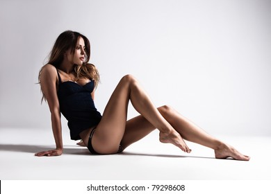 attractive tanned brunette in blue underwear sit on floor, full body shot, small amount of grain added, studio shot