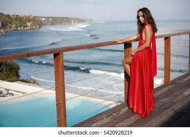 attractive tanned brunette girl in a long red dress is standing on a wooden terrace. sea view and infinity pool in the background