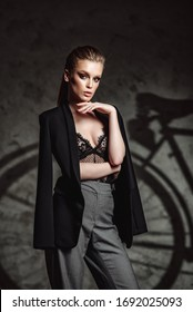 Attractive tanned brunette model in sexy lingerie, men's jacket posing against bike Shadow. Sexy girl with beautiful makeup. bike advertising concept.