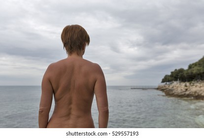 attractive tanned naked middle aged woman standing back to the camera on the background of the overcast Mediterranean sea and the coast