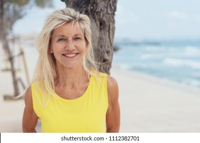 Attractive tanned older blond woman standing on a beach leaning against a tree grinning happily at the camera