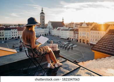 Attractive tanned woman in Ceske Budejovice with hat during sunrise when looking cityscape from balcony. Morning on roof with view the Samson fountain at square of King Premysl. CZECH REPUBLIC
