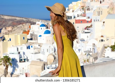 Attractive tanned woman in Oia village repairs herself with hat from the sun when looking cityscape from balcony in Santorini Island, Greece