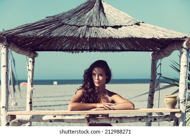 attractive tanned young woman relaxing on wooden bench under the shade of bamboo on the sand beach