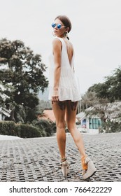 attractive tanned young woman in town wearing white short dress, boots on platform, sunglasses