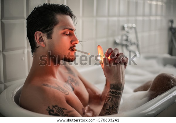 Attractive Tattooed Guy Smoking Cigarette While Stock Photo Edit Now 570633241