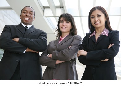 An attractive team of diverse business people smiling at company