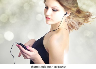 Attractive teen age girl listening to music with mp3 player and earphone with hair blowing in the wind on bokeh background