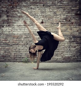 Attractive teen girl dancing outdoor against grunge bricks wall. Toned.