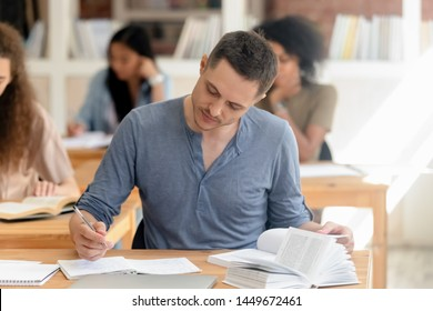 Attractive teen guy studying with textbook in classroom, writing notice, sitting at desk, college university student preparing assignment, passing final exam with multinational diverse classmates