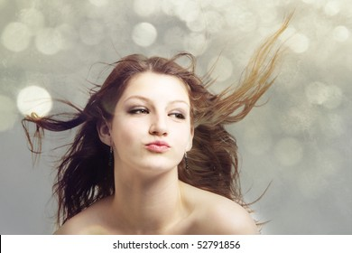 Attractive teenage girl model with hair blowing in the wind isolated on green bokeh background