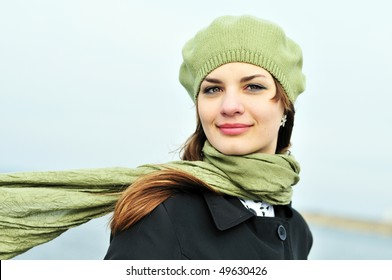 attractive teenage girl wearing beret standing outdoors in windy day