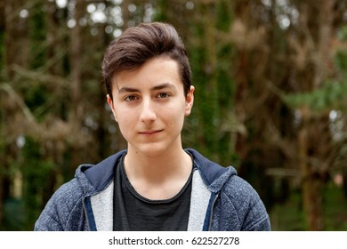 Attractive teenager guy in a park with green plants of background
