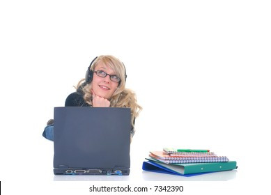 Attractive teenager schoolgirl with headphones, listening to music on laptop, books and pen on the side.  White background.