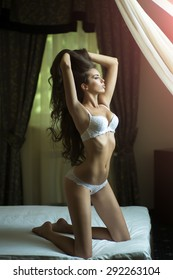 Attractive tender sexual young undressed brunette woman with straight body in white erotic lingerie sitting on bed in bedroom looking out the window in the morning, vertical picture