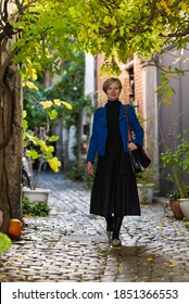 Attractive thirty year old white woman in a long dress walking down a narrow street with cobble stones