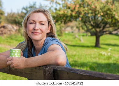 Attractive thoughtful middle aged woman leaning resting on fence in the countryside with mug or cup of tea or coffee